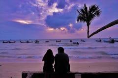 现出轮廓在海滩的爱夫妇观看的日落 图库摄影