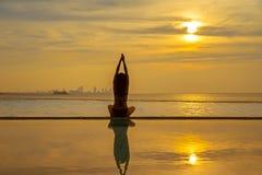 现出轮廓在游泳池和海滩的少妇实践的瑜伽在日落 库存照片