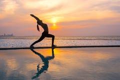 现出轮廓在游泳池和海滩的少妇实践的瑜伽在日落 免版税库存照片