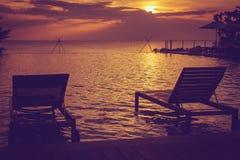 现出轮廓在游泳池的沙发床有美好的海景视图和日落在背景中 库存图片