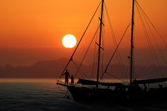 现出轮廓在游艇的家庭有红色天空日落的 免版税库存照片