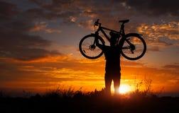 现出轮廓在行动举的自行车的人立场在他的头上 库存图片