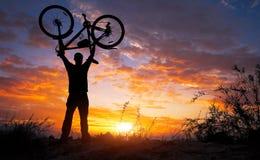 现出轮廓在行动举的自行车的人立场在他的头上 免版税库存照片
