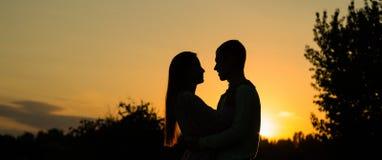 现出轮廓夫妇亲吻在日落背景的,看彼此的浪漫夫妇外形在日落背景  图库摄影