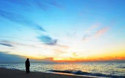 现出轮廓妇女,在海洋友好点海滩,北部Stradbroke海岛,澳大利亚的日落 库存图片
