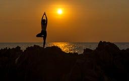 现出轮廓少妇行使重要在海滩思考和实践的瑜伽在日落的生活方式 免版税库存照片