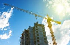 现出轮廓建筑用起重机设备、工业建筑用起重机和大厦在惊人的日落天空摘要 库存图片