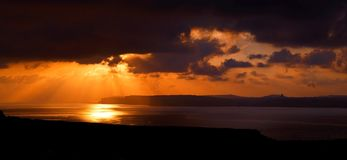 现出轮廓戈佐岛的黄褐色和多云日落 库存照片