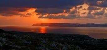 现出轮廓戈佐岛的黄褐色和多云日落 免版税库存图片
