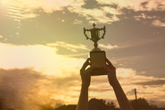 现出轮廓拿着优胜者在冠军的手战利品杯子 免版税库存图片