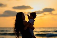 现出轮廓有使用和微笑在海滩的女儿的年轻母亲对日落 幸福家庭和旅行概念 库存照片