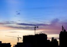 现出轮廓有起重机的建造场所反对多云天空在S 库存照片