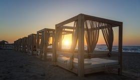 现出轮廓木与在一个空的沙滩的窗帘眺望台在日落背景 库存照片