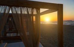 现出轮廓木与在一个空的沙滩的窗帘眺望台在日落背景 免版税图库摄影