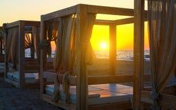现出轮廓木与在一个空的沙滩的窗帘眺望台在日落背景 库存图片