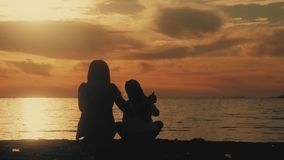 现出轮廓母亲,并且女儿坐海滩在日落 友好的家庭的概念,生活方式 影视素材
