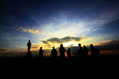 现出轮廓游人和菩萨雕象与美好的日出在山 库存照片