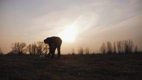 现出轮廓父亲和小儿子有踢足球在草甸的球的在日落时间 友好的家庭的概念 股票视频