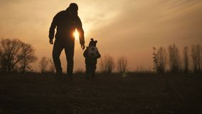 现出轮廓父亲和小儿子有踢足球在草甸的球的在日落时间 r 股票视频