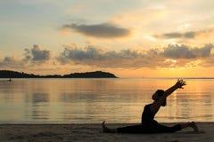 现出轮廓瑜伽女孩在海滩的日出 免版税图库摄影