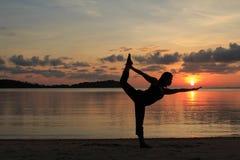 现出轮廓瑜伽女孩在海滩的日出 免版税库存图片