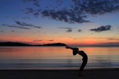 现出轮廓瑜伽女孩在海滩的日出 库存照片