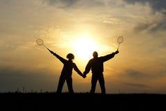 现出轮廓男人和妇女的对作为丈夫和妻子天空黄色日落的 库存照片