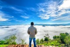 现出轮廓站立在一个高小山风景农村故乡的年轻人 免版税库存图片