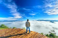 现出轮廓站立在一个高小山风景农村故乡的年轻人 免版税图库摄影