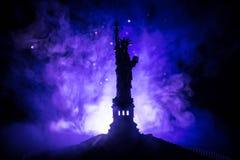 现出轮廓自由女神象在黑暗的被定调子的有雾的背景的 在五颜六色的黎明天空背景的自由女神像  免版税库存图片