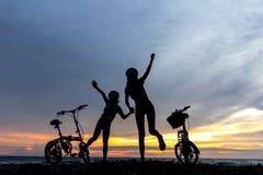 现出轮廓自由骑自行车的人可爱的家庭在海洋的日落 免版税库存图片