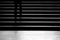 现出轮廓走城市台阶的人的阴影 免版税图库摄影