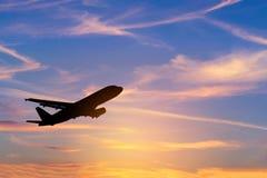现出轮廓飞行到天空的乘客飞机在日落期间 免版税图库摄影