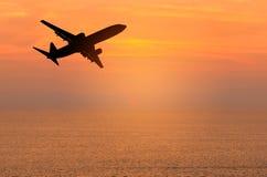 现出轮廓飞行到高昂的高度的乘客飞机在日落时间 免版税库存图片