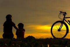 现出轮廓骑自行车的人可爱的家庭在海洋的日落 骑自行车在海滩的妈妈和女儿 库存图片