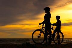现出轮廓骑自行车的人可爱的家庭在海洋的日落 骑自行车在海滩的妈妈和女儿 图库摄影