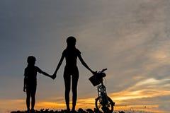现出轮廓骑自行车的人可爱的家庭在海洋的日落 骑自行车在海滩的妈妈和女儿 库存照片
