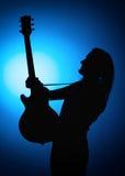 现出轮廓一个摇滚乐队的吉他弹奏者与吉他的在蓝色背景 库存照片