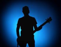 现出轮廓一个摇滚乐队的吉他弹奏者与吉他的在蓝色背景 免版税图库摄影
