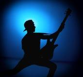 现出轮廓一个摇滚乐队的吉他弹奏者与吉他的在蓝色背景 免版税库存图片