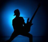 现出轮廓一个摇滚乐队的吉他弹奏者与吉他的在蓝色背景 免版税库存照片