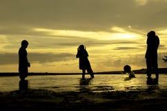 现出轮廓三男孩戏剧海滩球和片刻落在日落日出期间的球 免版税库存照片