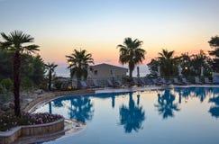 现出轮廓与伞的可可椰子树和椅子在日出时间在室外游泳池附近 图库摄影