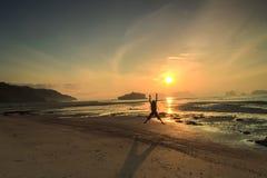 现出轮廓人和日落与e的海滩假期假日 免版税图库摄影