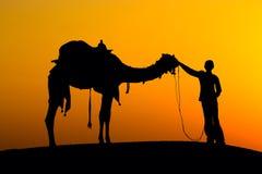 现出轮廓人和骆驼在日落在印度 库存照片