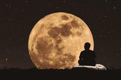 现出轮廓人坐的放松在满月下在与星的晚上在天空 免版税库存照片