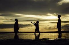 现出轮廓使用在海滩的年轻男孩的图象概念有美好的日出日落背景 免版税库存照片