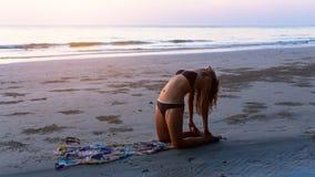 现出轮廓做在惊人的海的背景的女孩锻炼 库存照片