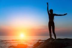 现出轮廓凝思实践在日落的女子平静和瑜伽 健身 免版税库存照片