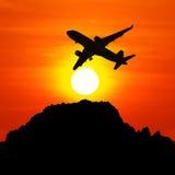 现出轮廓在天空的飞机在晚上日落 库存图片